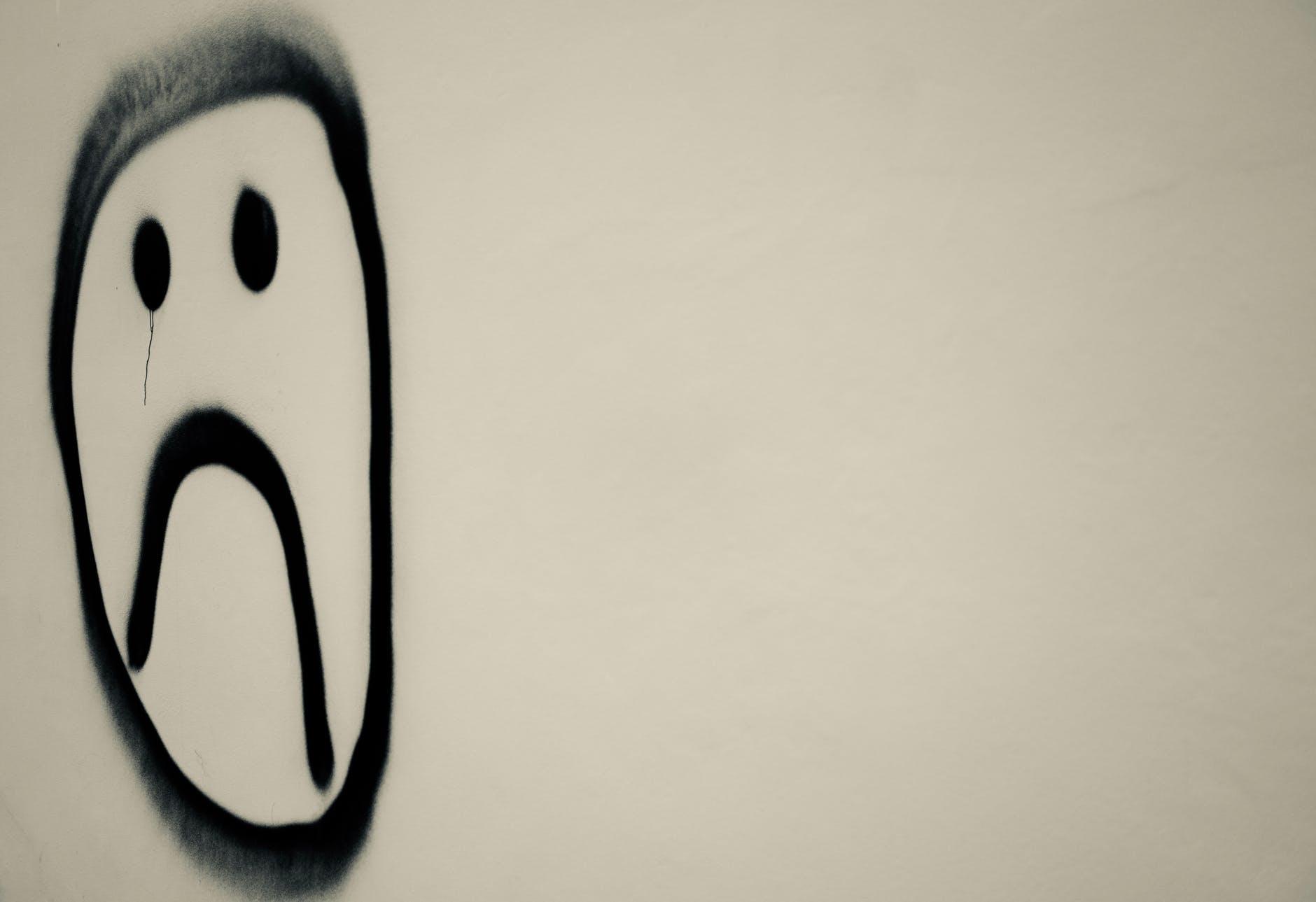Surullinen hymiö seinällä